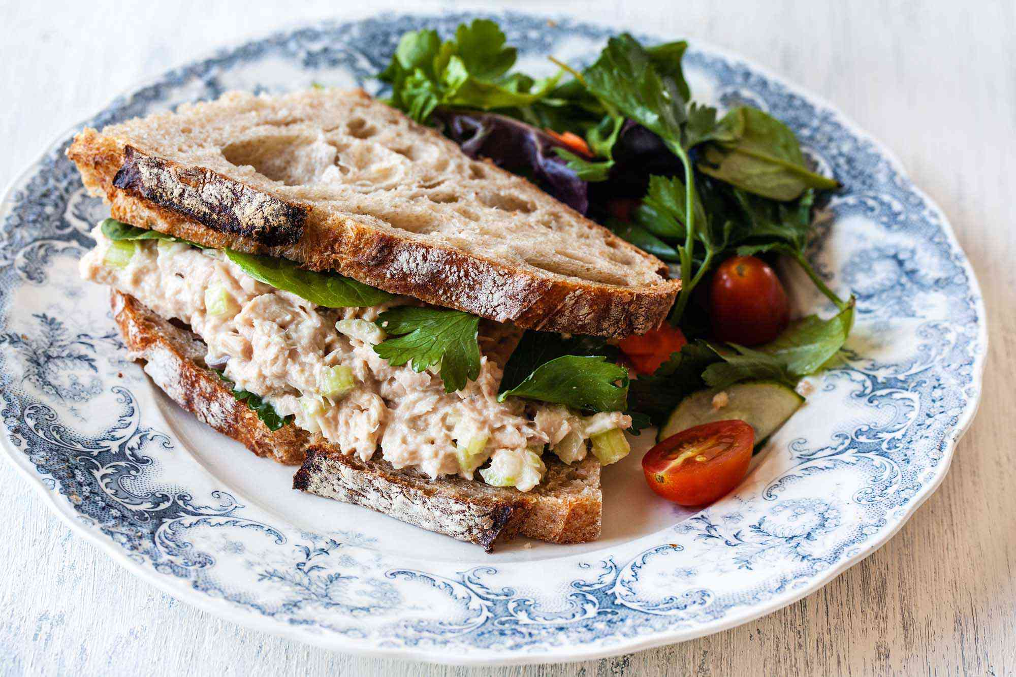 Crusty sandwich bread with the best tuna salad inside. A green salad of lettuce and tomato halves is to the left on the china.