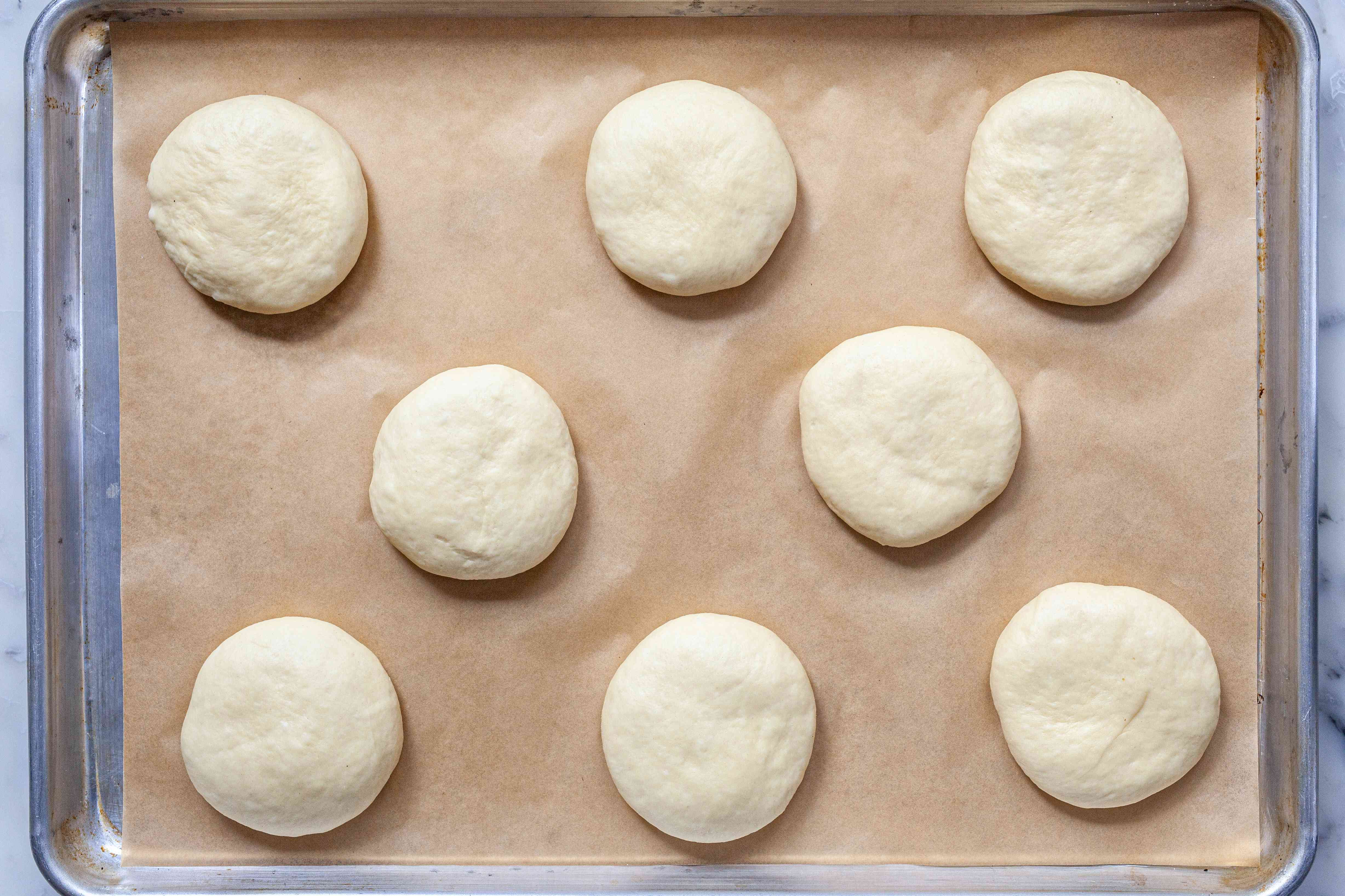 Burger buns ready to be baked on a baking sheet.
