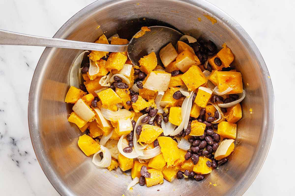 Butternut Squash and black beans in a bowl for vegetarian enchiladas.