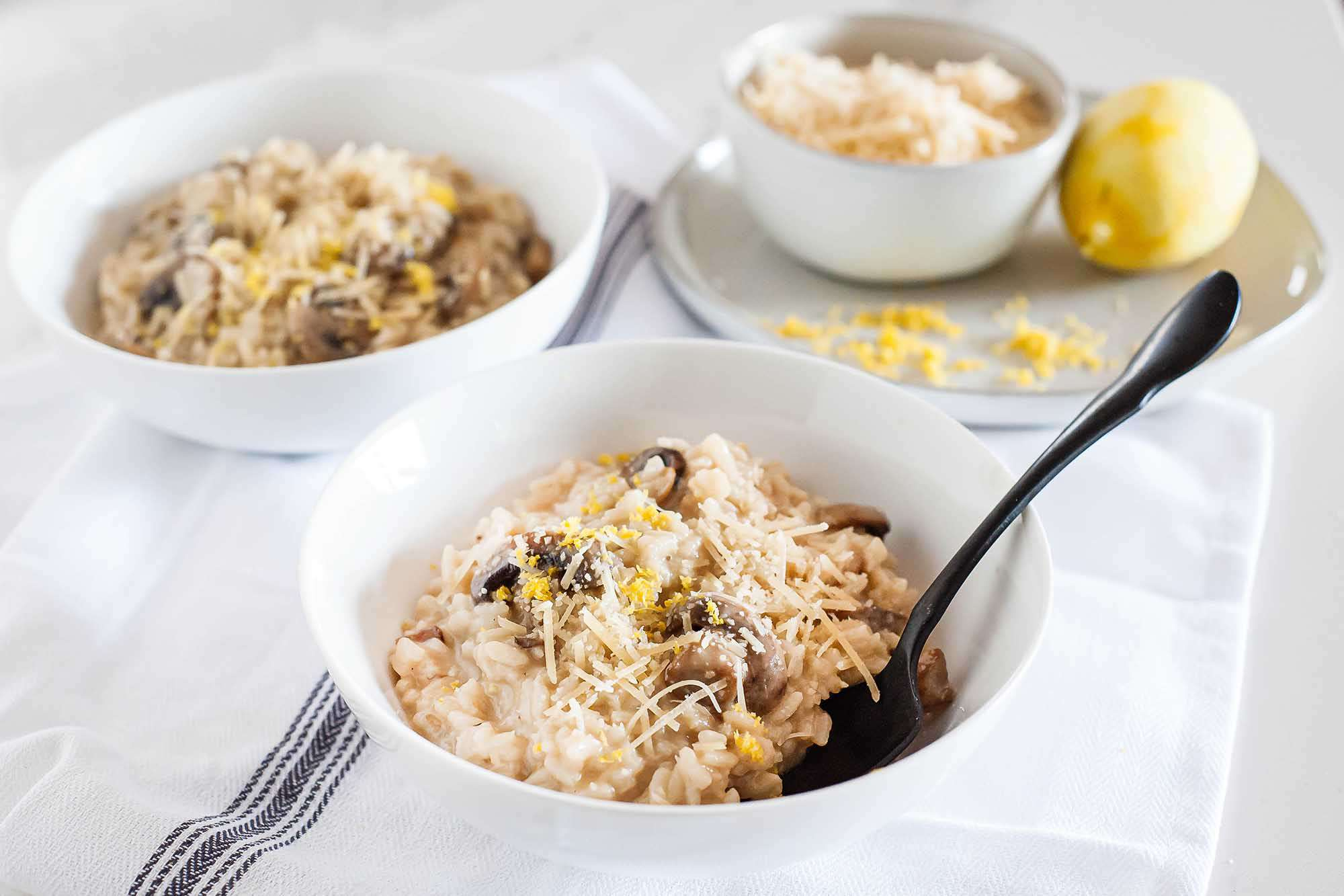 Risotto with Mushrooms - white bowls filed creamy mushroom risotto
