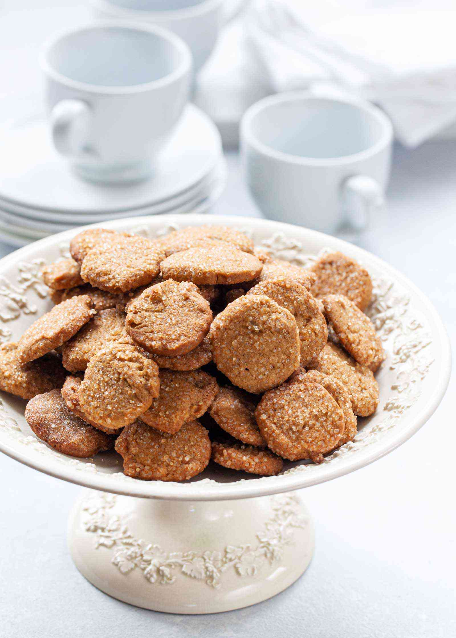 Make Ahead Slice and Bake Ginger Cookies heaped on a cake stand with coffee mugs and dessert plates set behind.