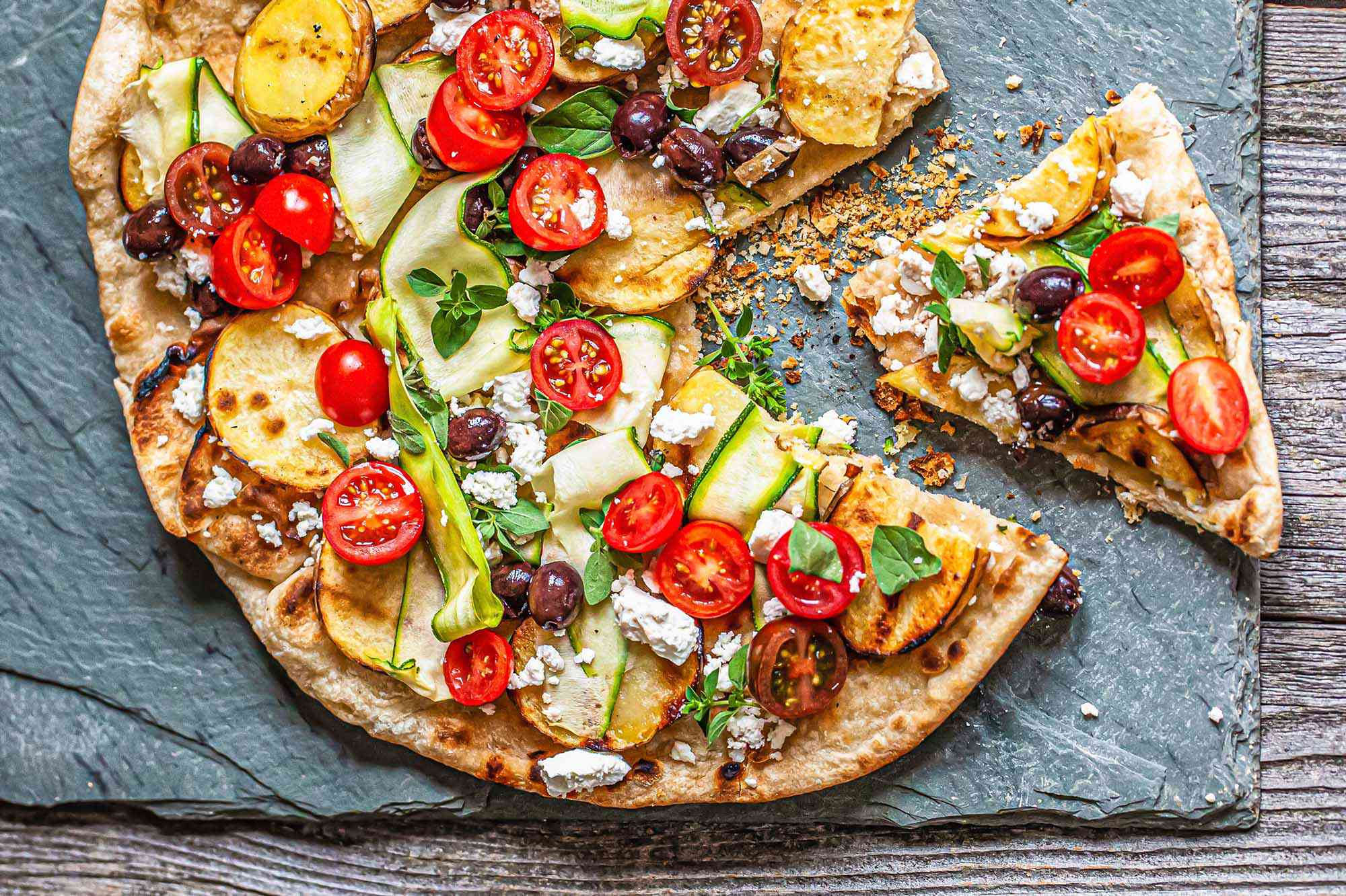 The best grilled pizza topped with halved tomatoes, black olives, cheese, zucchini ribbons and sliced potatoes. The pizza is set on a slate background and a piece on the right is pulled away from the rest.