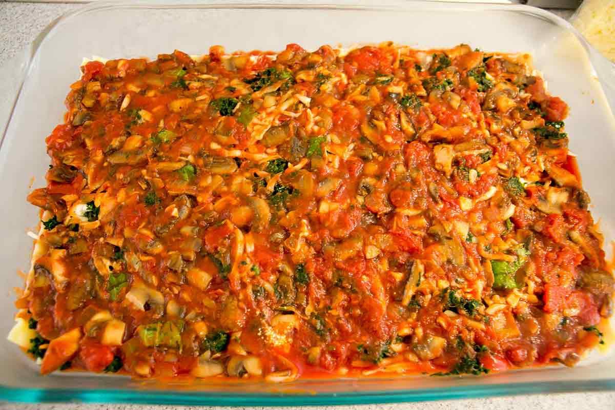 Veggie lasagna adding the sauce layer