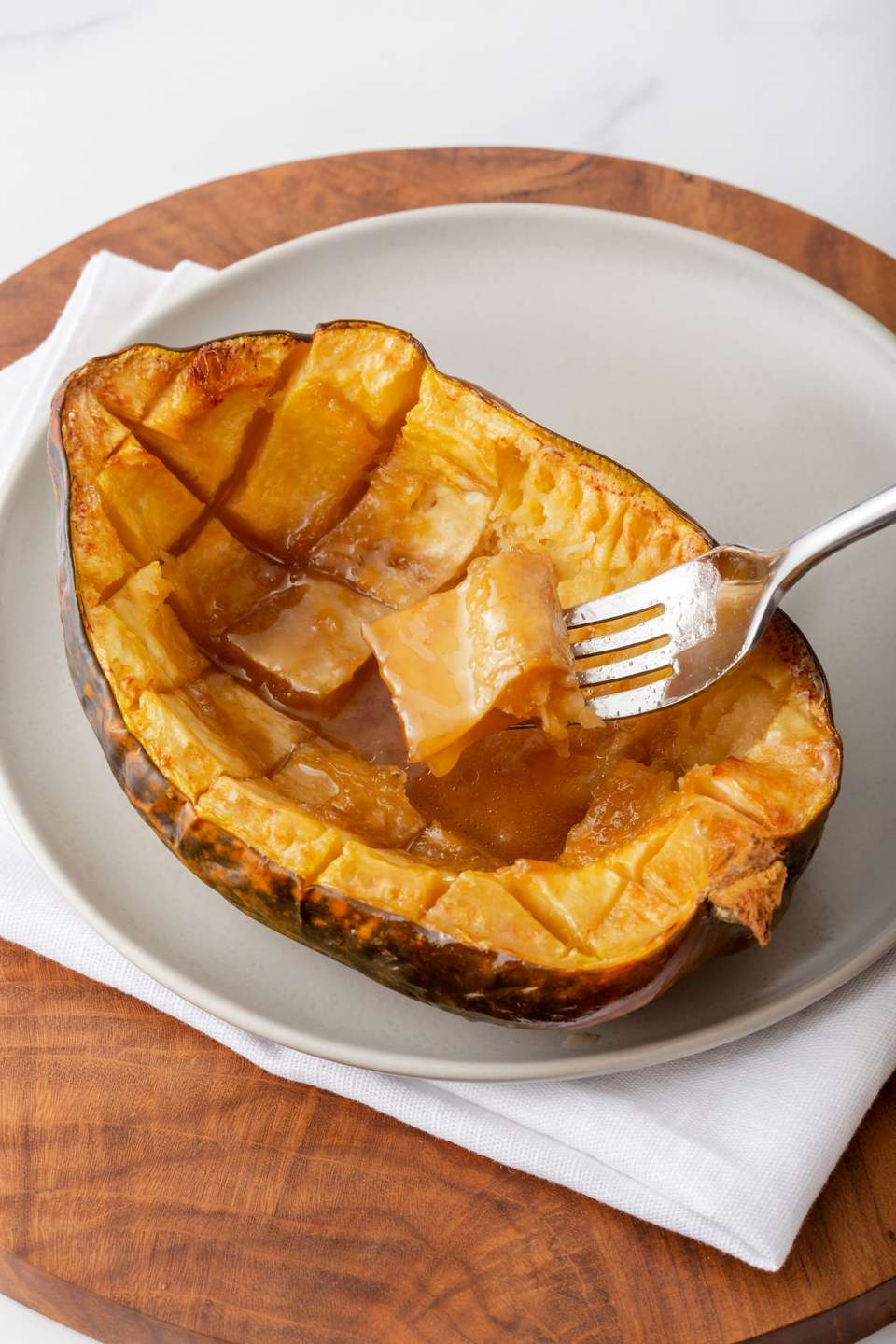 A plate of roasted squash with a fork taking a piece.