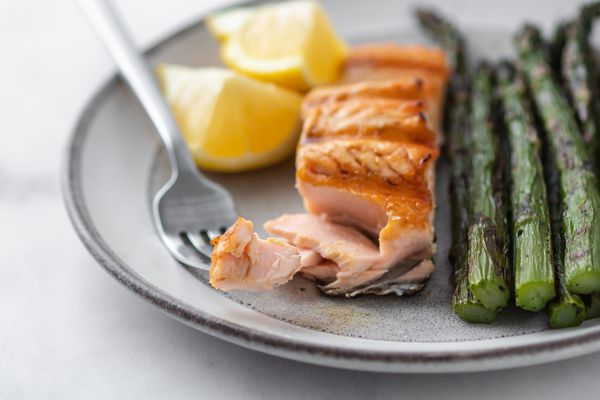 Grilled salmon with a forkful taken out alongside asparagus and lemon on the plate.