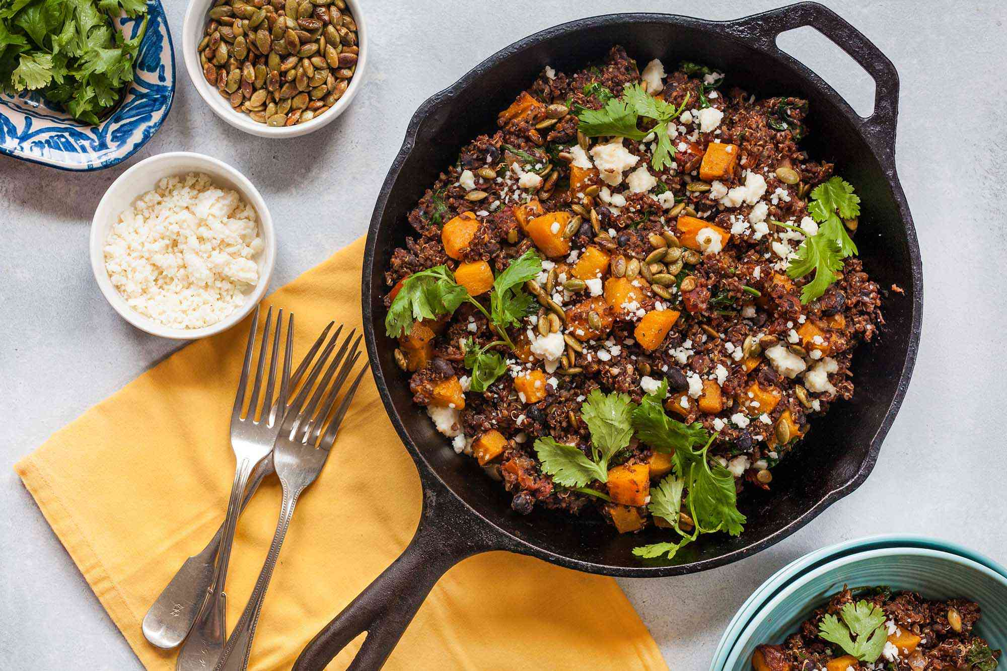 Horizontal view of a large cast iron skillet filled with a butternut squash skillet dinner. Cilantro, quinoa, butternut squash and cotija cheese are visible in the pan. To the left is a yellow napkin with three forks on it. Above the forks are three small bowls. One small bowl of rice, a ramiken of roasted pumpkin seeds and a small platter of cilantro.