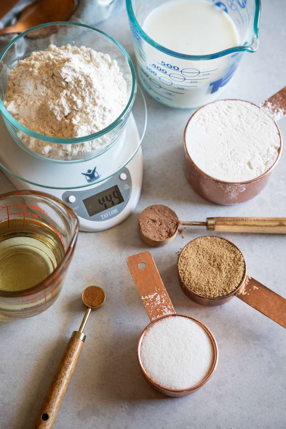 Measuring cups, scales, and liquid measuring to show how to measure flour.