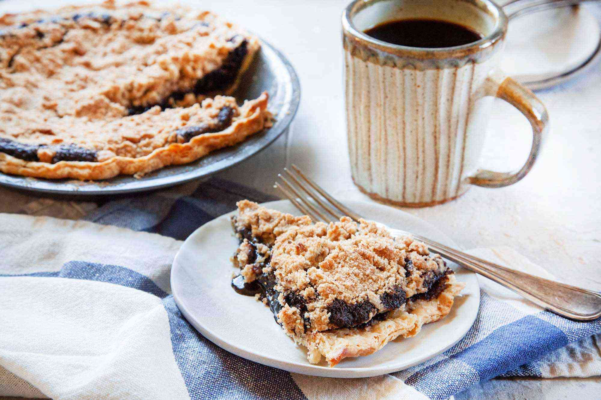 A slice of shoo fly pie on a plate with the rest of the pie behind it along with a cup of coffee.