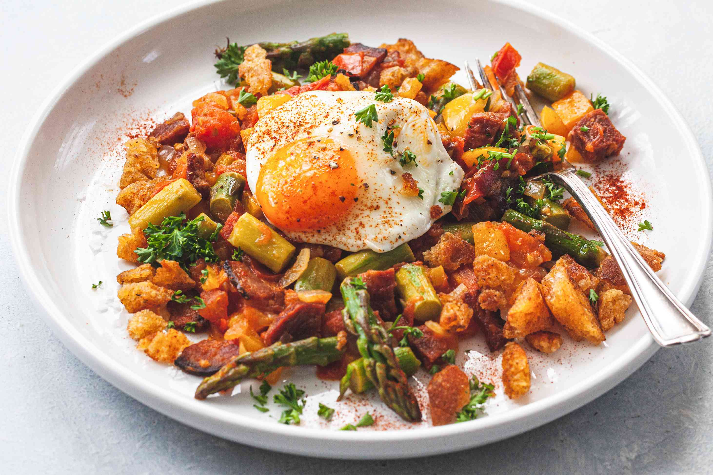 A white plate with Spanish Style Migas with Asparagus, Chorizo, Bacon, and Eggs.
