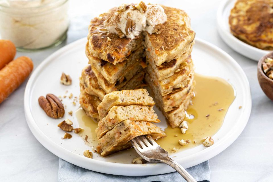 Tall stack of buttermilk carrot cake pancakes with a cream cheese topping, chopped pecans and a puddle of syrup at the bottom of the plate. Whole carrots, a glass of cream cheese topping, more pancakes and a bowl of chopped pecans surround the plate.