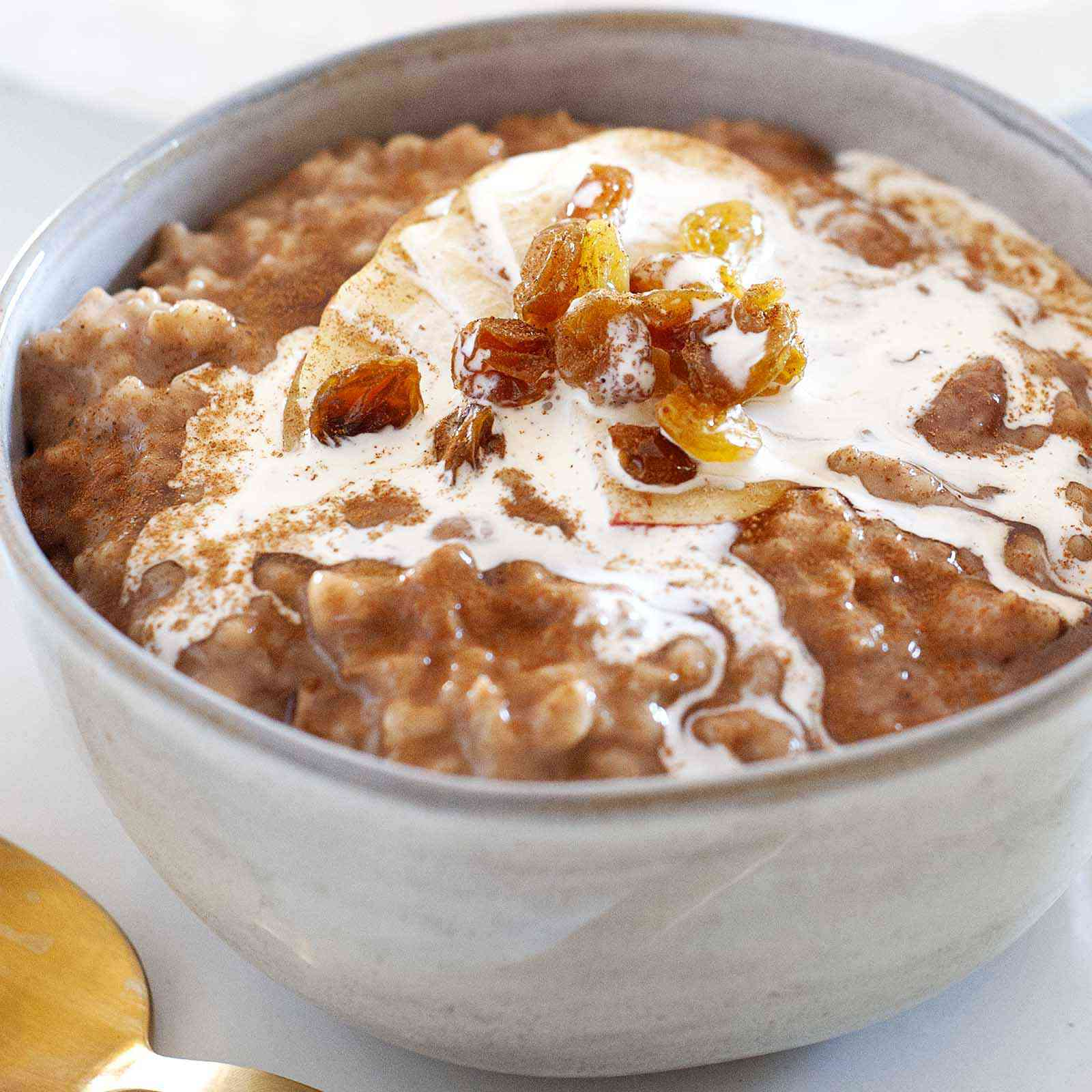 Crockpot Oatmeal topped with milk and golden raisins with a gold spoon below.