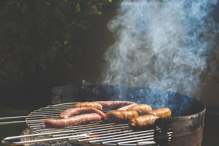 A barbeque full of sausages ready to eat