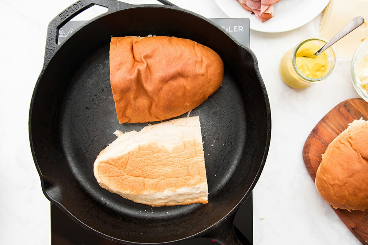 A cast iron skillet is set on a bunsen burner. Half of a loaf of french bread that has been lengthwise is being toasted to make the best cuban sandwich. A plate of sliced ham and sliced cheese is visible on the right side, along with a wooden cutting board and the other half of the french bread.