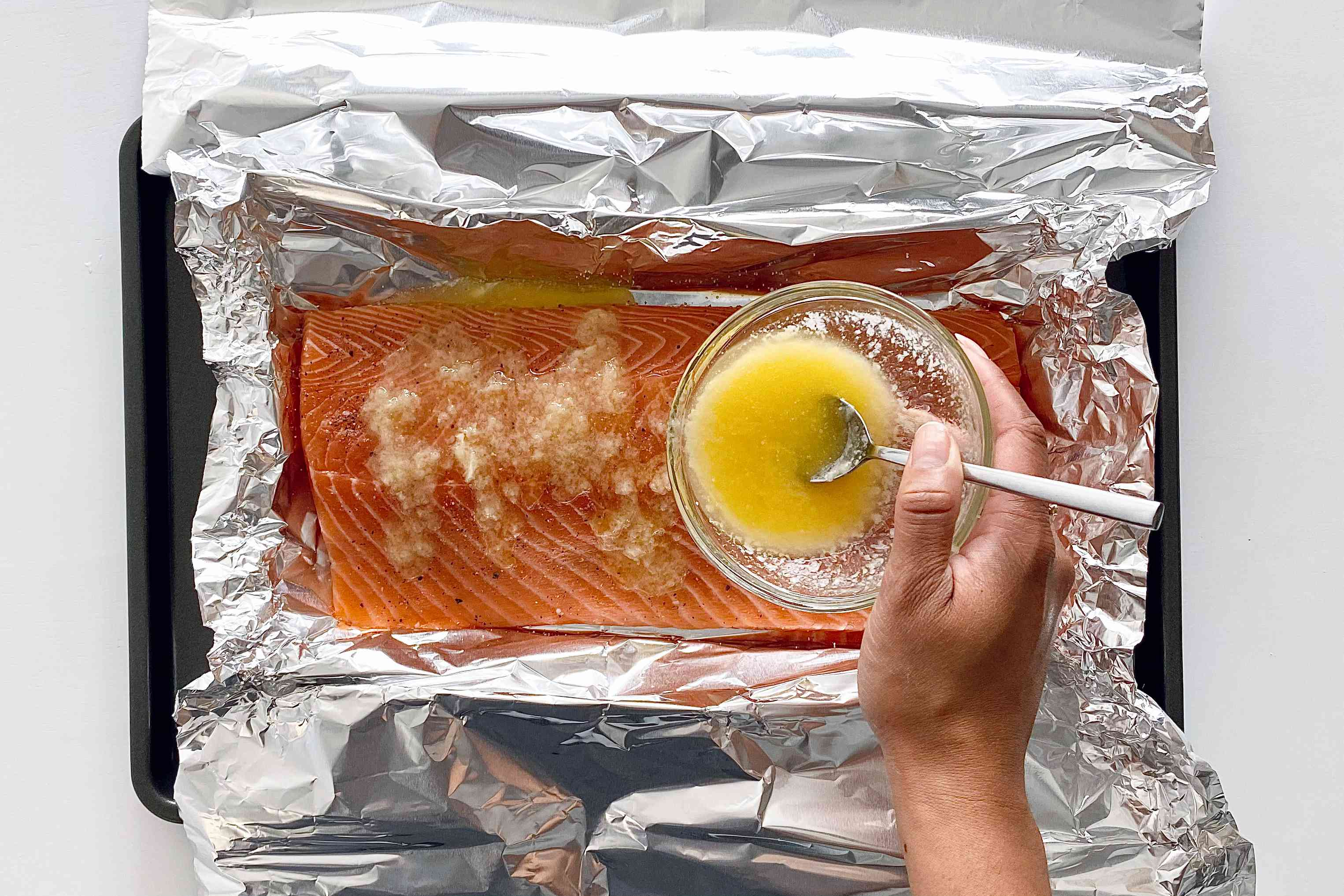 Making a Roasted Side of Salmon by pouring melted butter on the unbaked salmon.