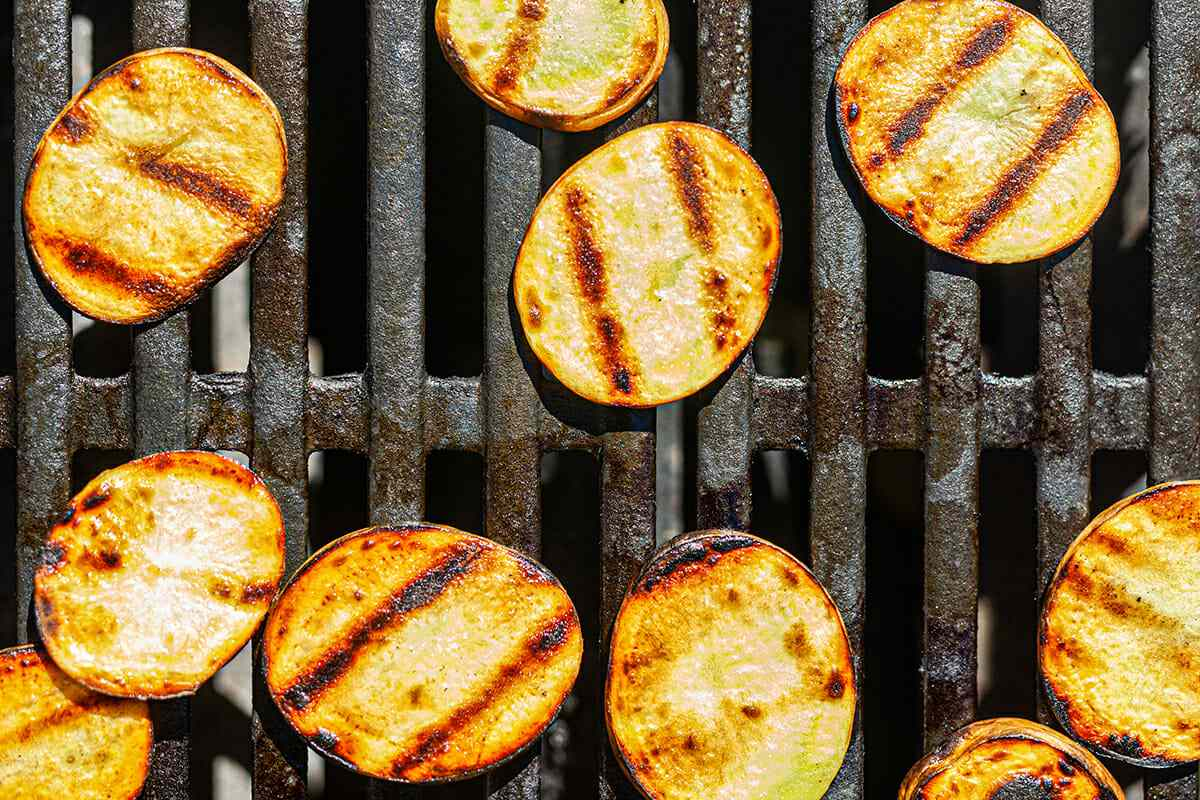 Zucchini coins on the grill with grill marks to make a grilled vegetable pizza.