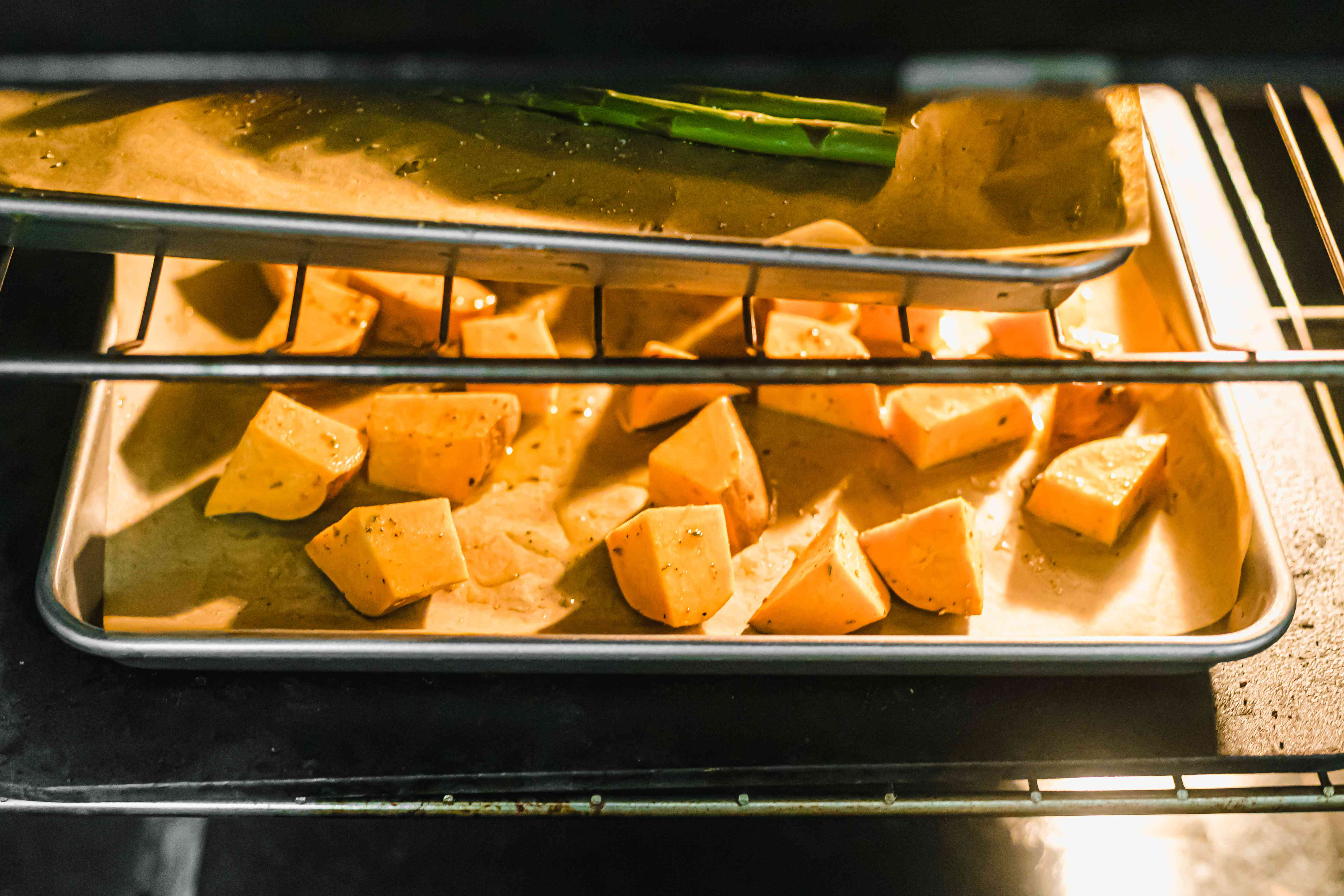 Sweet potatoes on a sheet pan roasting in the oven