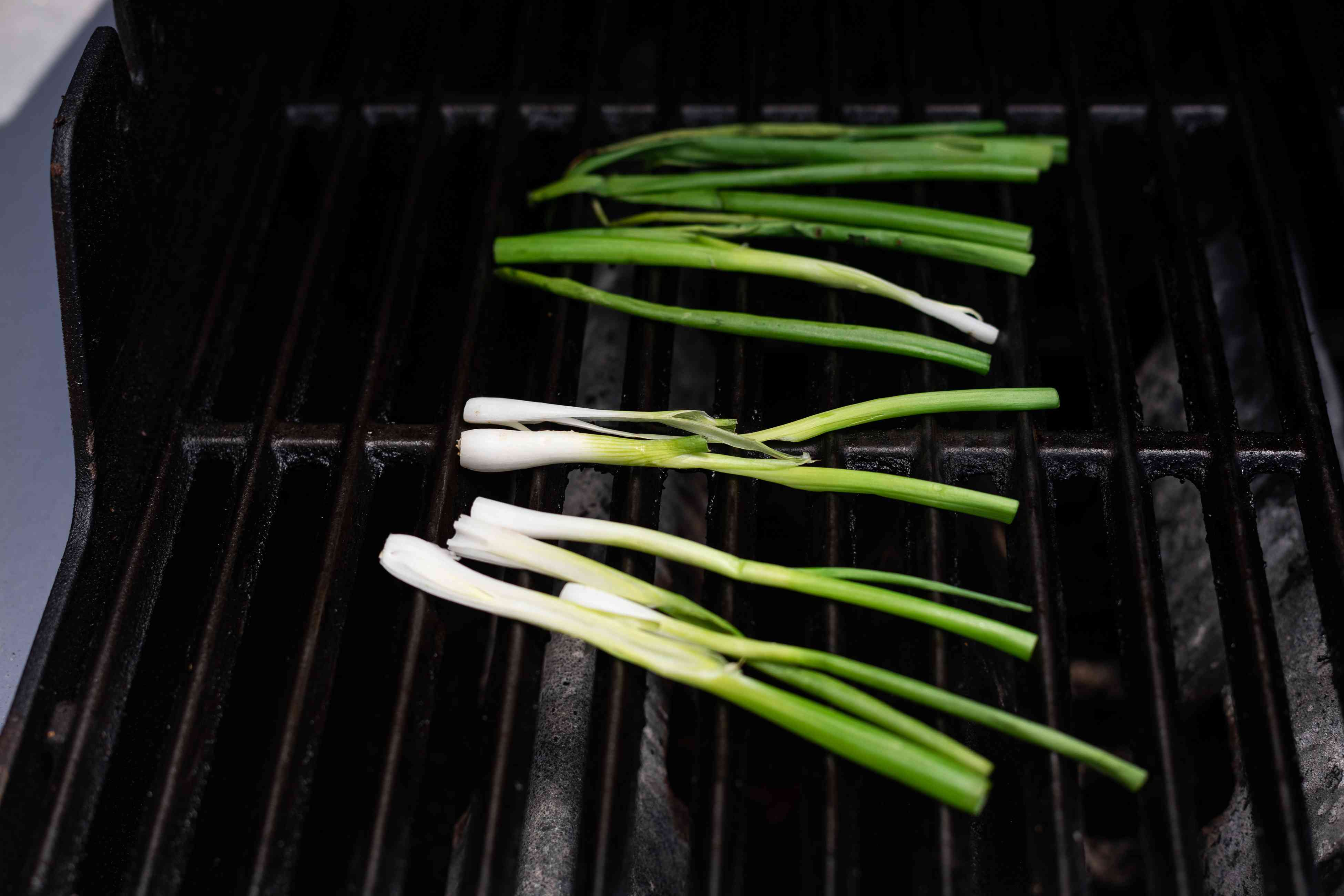 Grilling scallions to make grilled cabbage with peanut satay sauce.