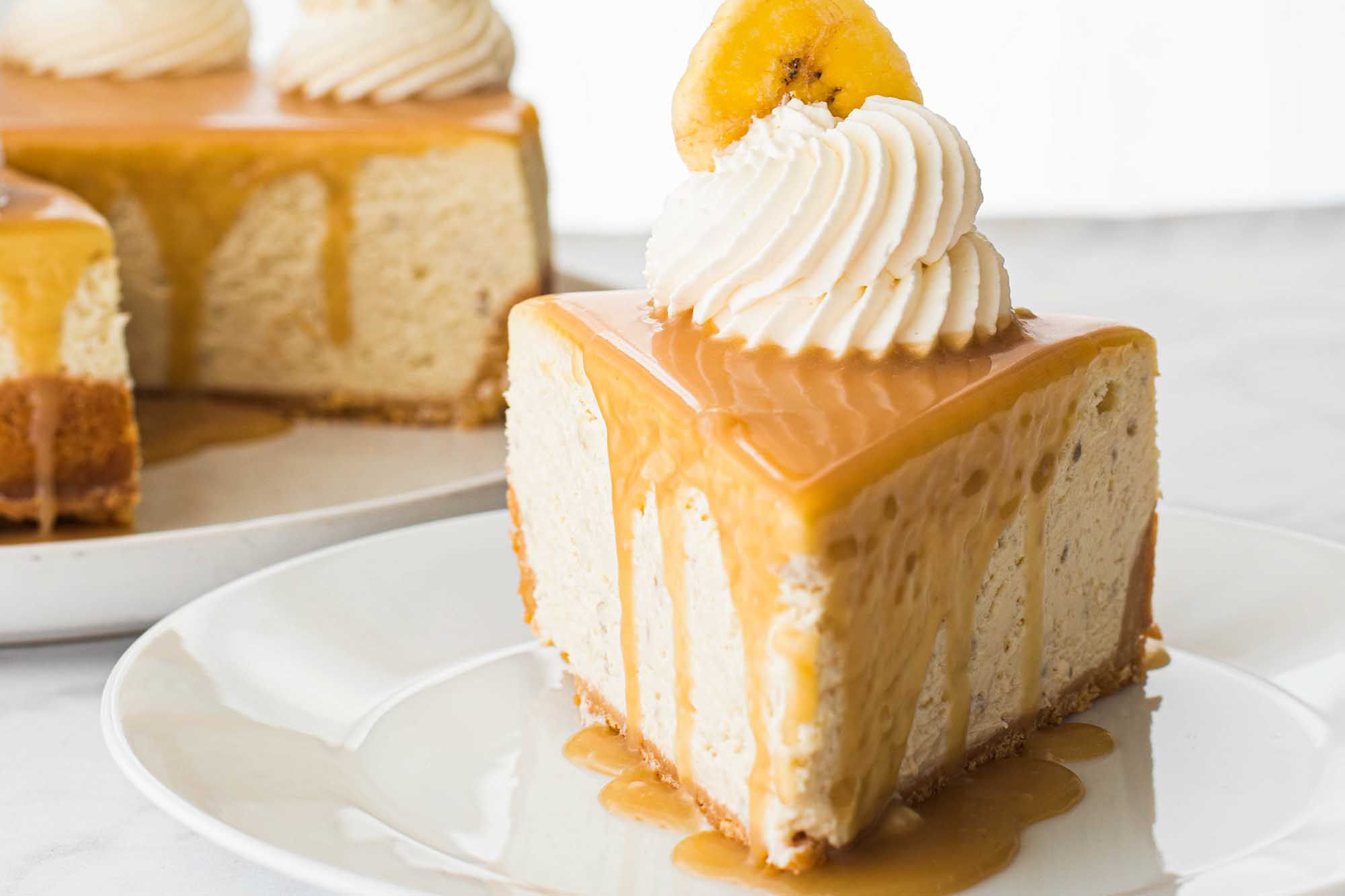 Easy Banoffee Cheesecake Pie - slice of pie with mound of whipped cream and banana slice