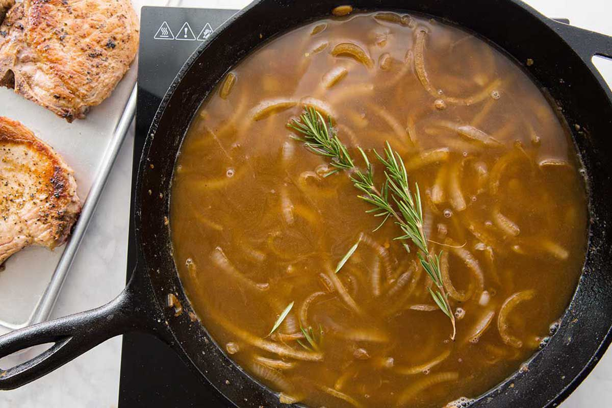 Onions with rosemary in a cast iron skillet filled with gravy and being stirred with a wooden spoon.