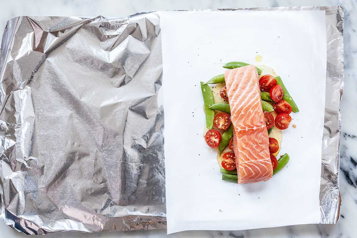 A large piece of foil is under a white piece of parchment paper. Uncooked salmon fillet covers halved grape tomatoes and sugar snap peas.