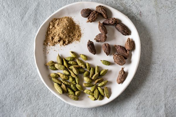 Ground cardamom and green and black cardamom pods on white plate