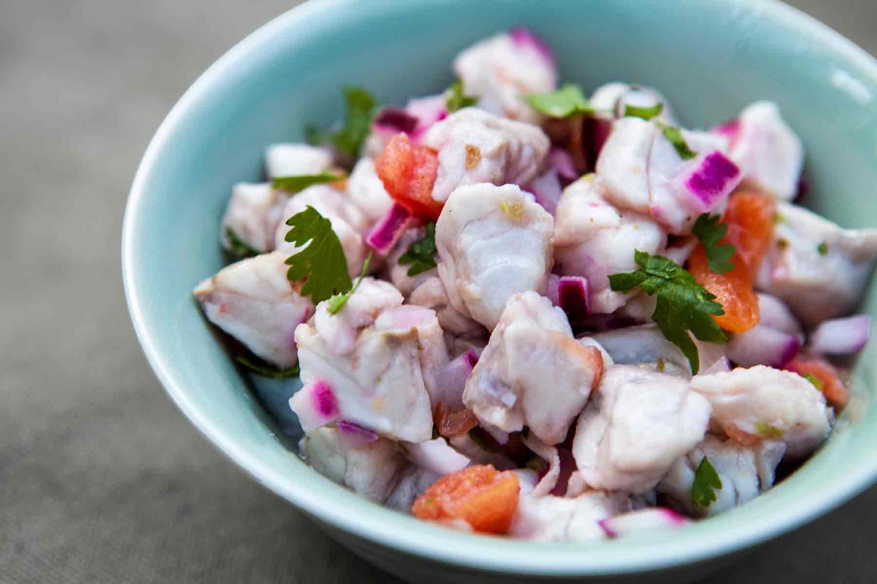 Ceviche with fish, onion, tomatoes, and chilis in a bowl