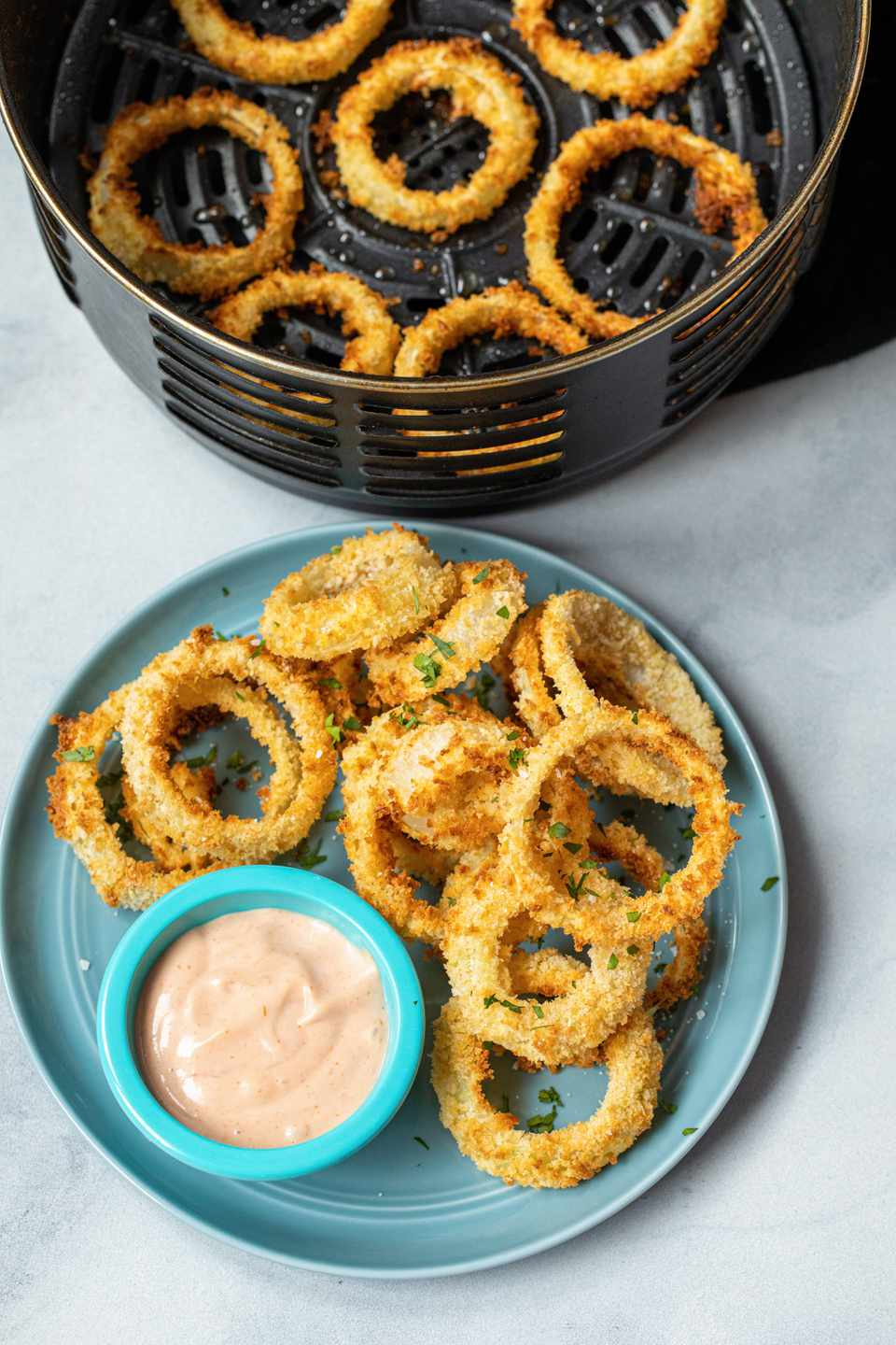 Crispy, Homemade Air Fryer Onion Rings on a plate with sauce and an air fryer basket with more onion rings behind the plate.