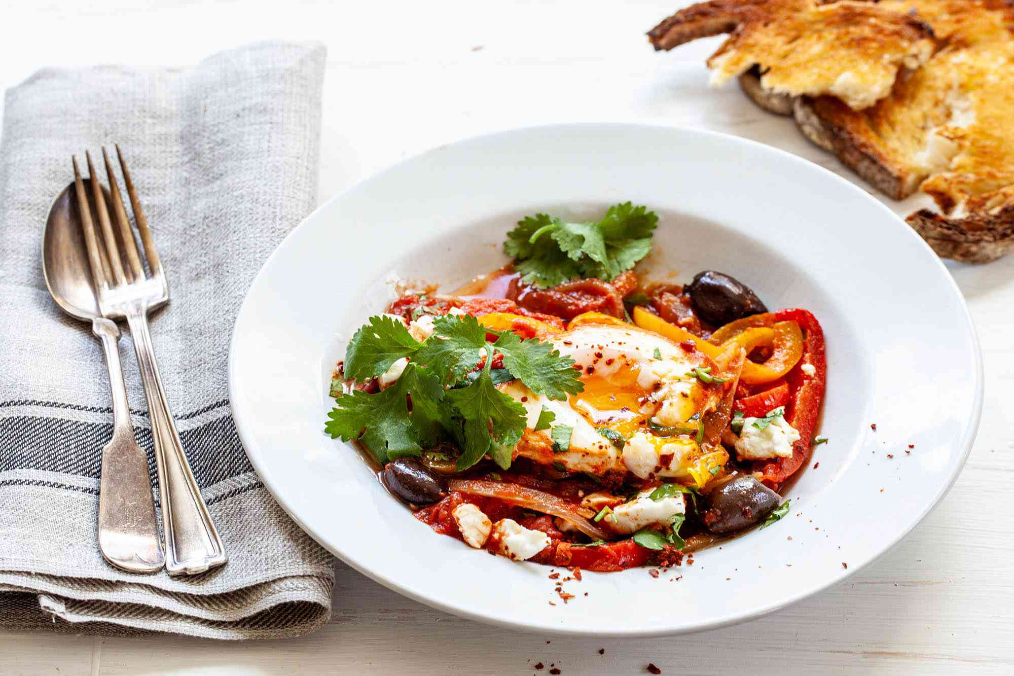 Best Shakshuka with a side of bread and topped with feta and olives.