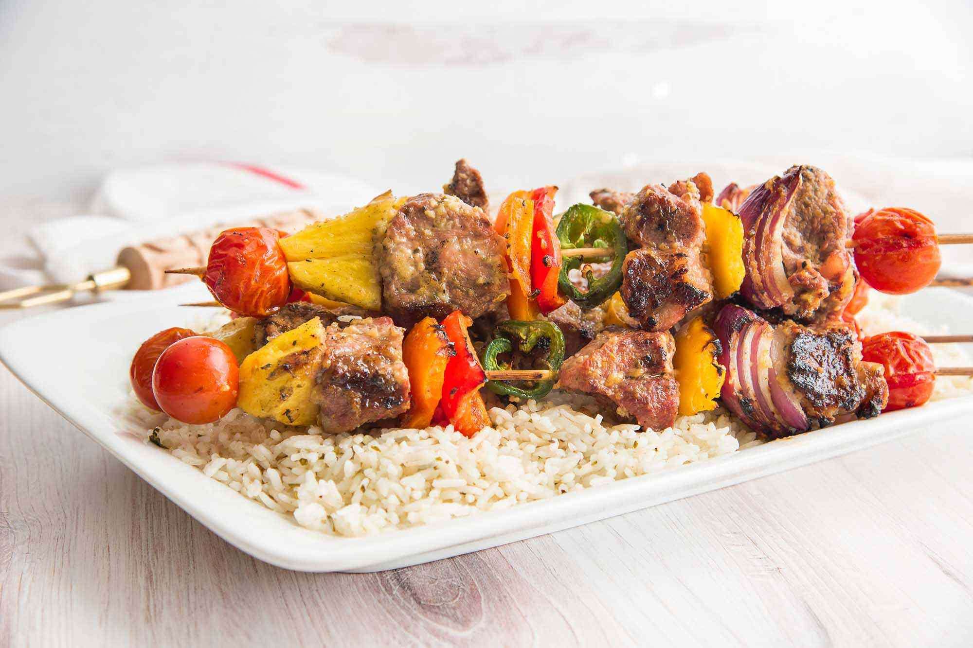 Pork kebabs with grilled pineapple and a rainbow of vegetables are on a platter along with rice.