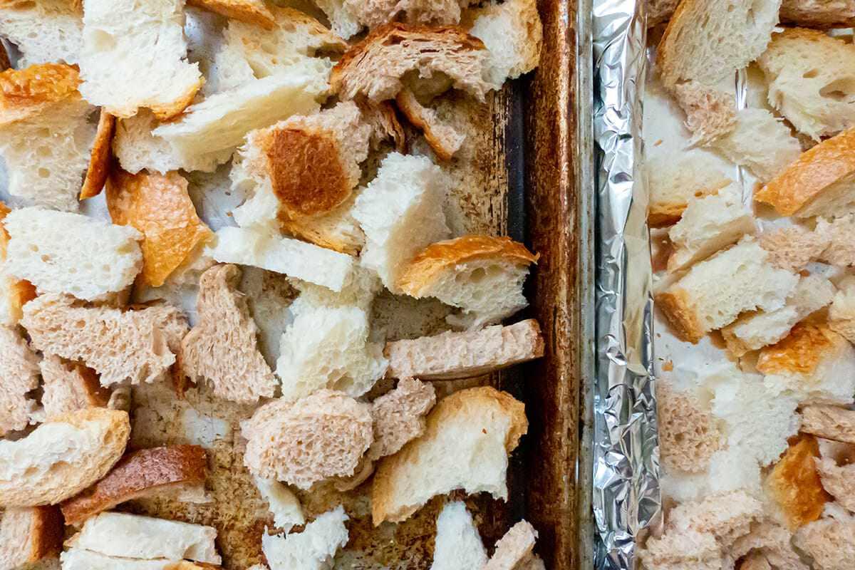 Torn bread on baking sheets to make Pumpkin Sage Strata.