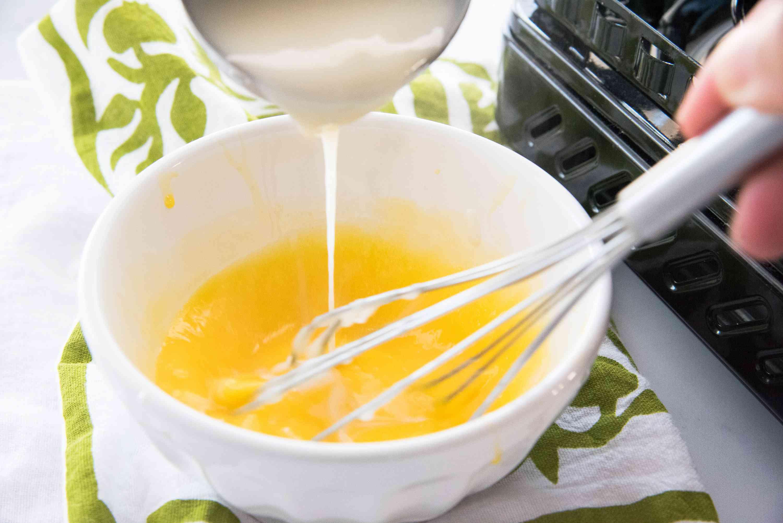 Adding cream to the egg mixture to make a German buttercream recipe.