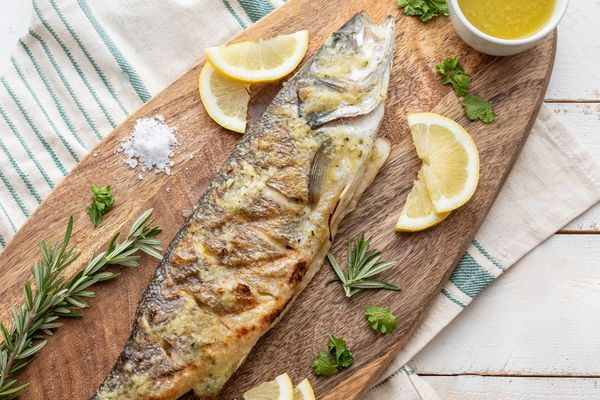 Overhead view of a whole branzino fish on a platter with lemon wedges and herbs.