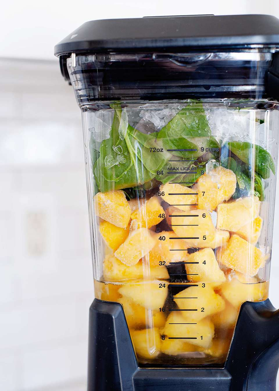 Close up view of a high speed blender jar with pineapple and spinach inside.