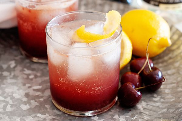 Homemade cherry pop cocktail with fresh cherries and lemon set next to it.