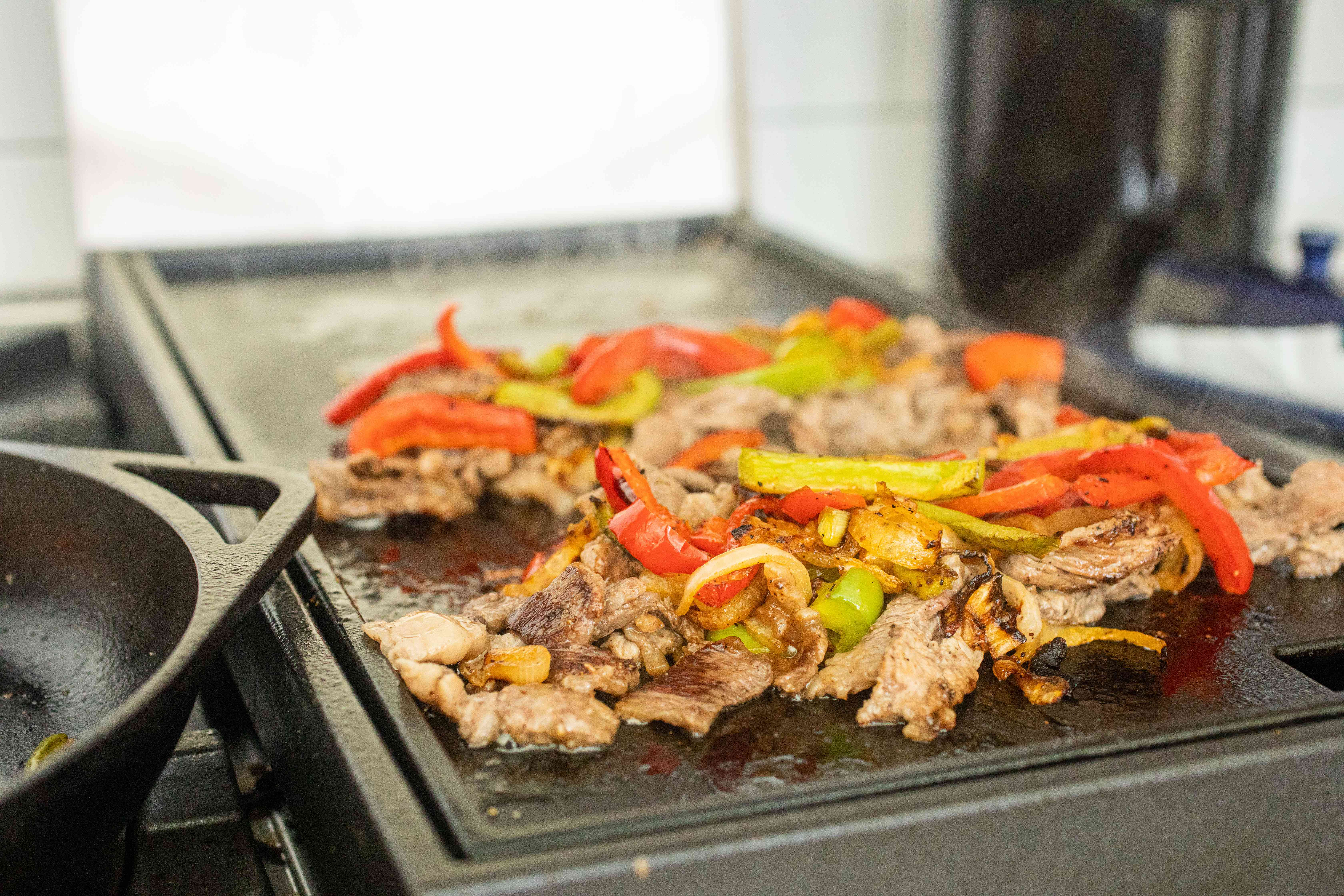 Peppers and beef cooking on a griddle to show how to make a Philly cheesesteak.