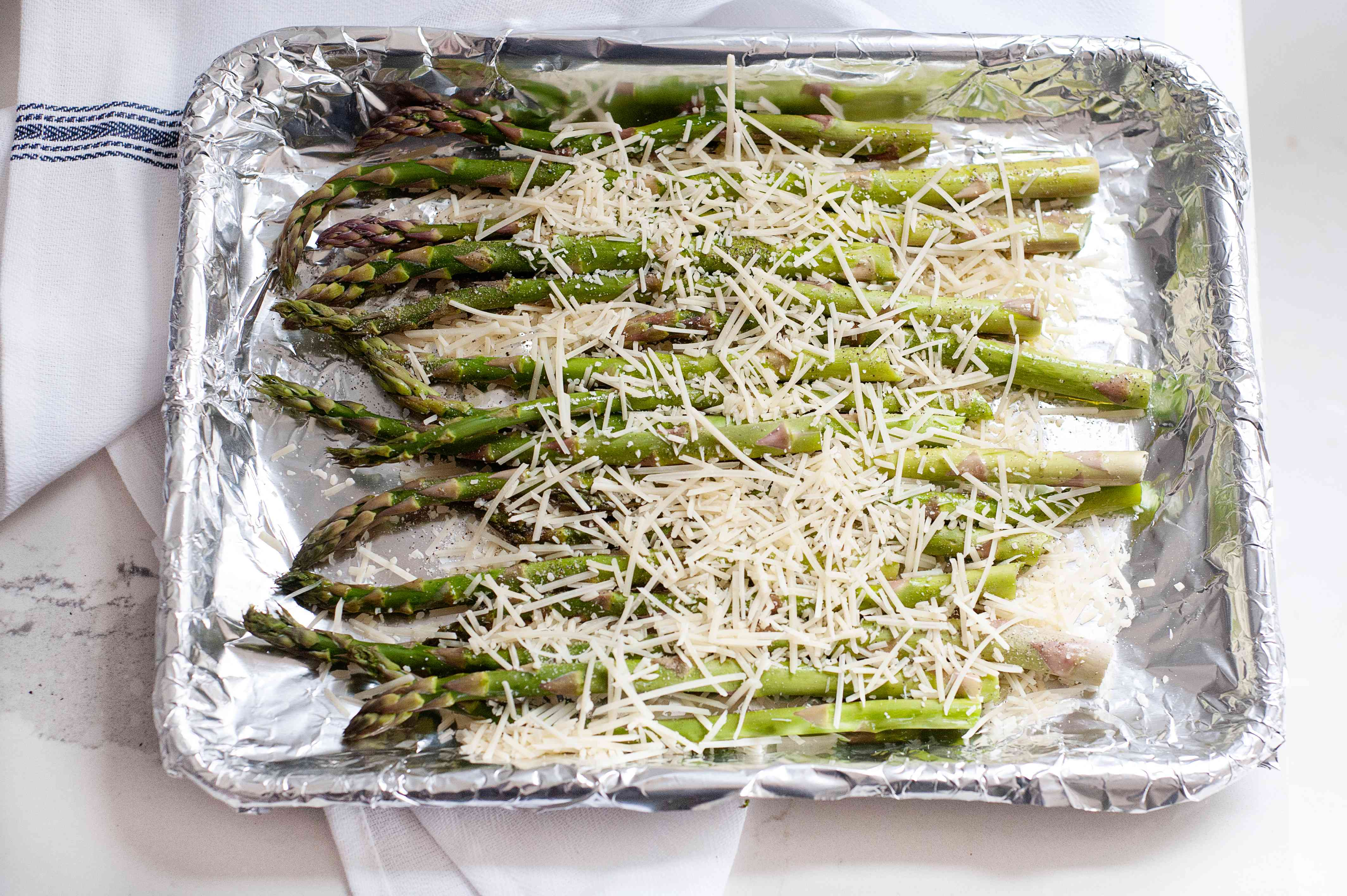 A baking tray with asparagus topped with parmesan to show how to cook asparagus in the oven.