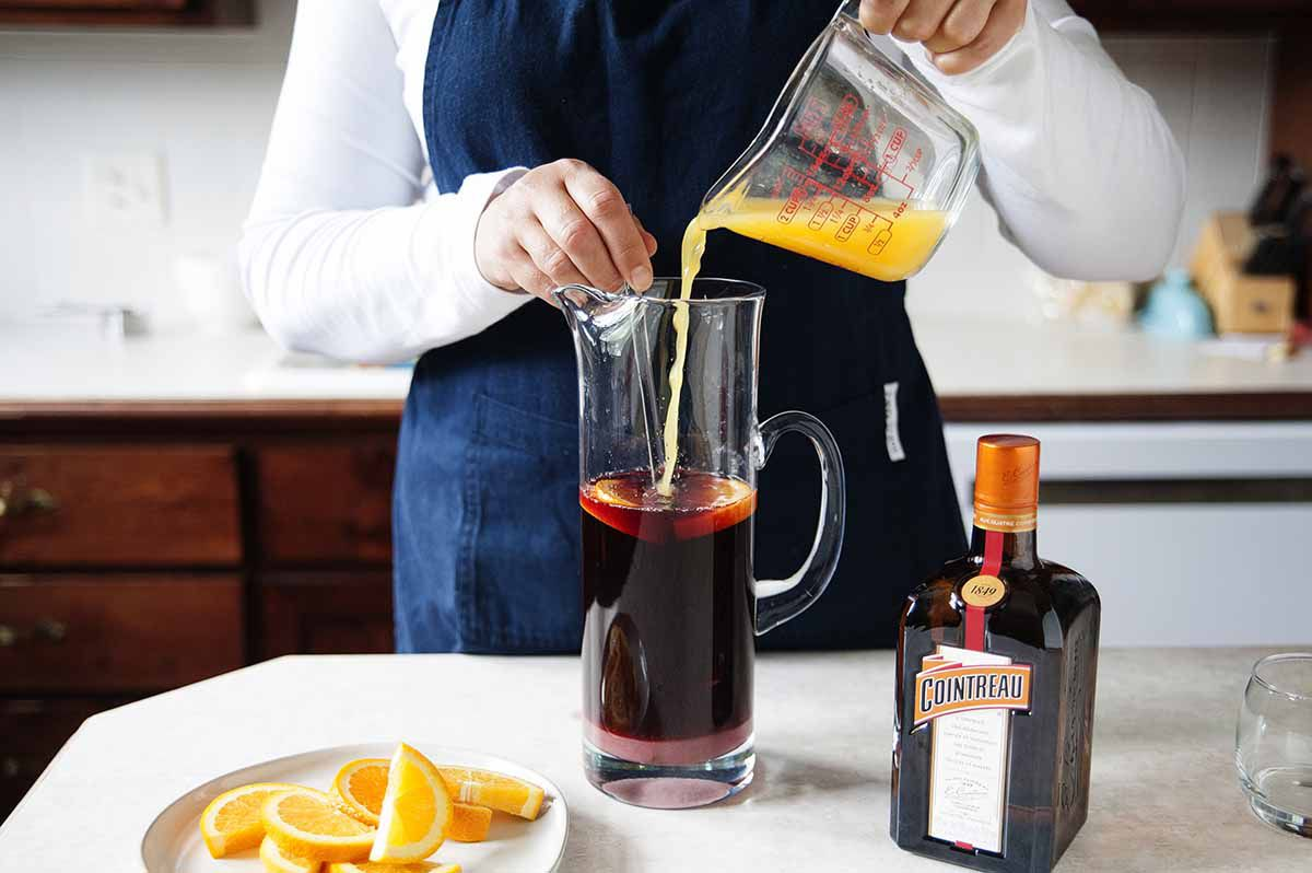 Red Wine Sangria Recipe - orange slices in a pitcher of sangria on a silver tray with two poured glasses of sangria