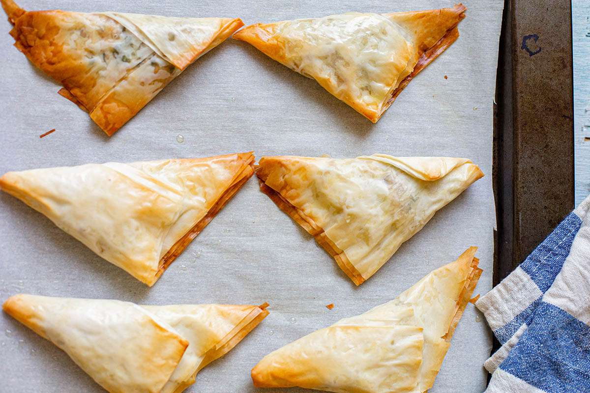 Baked Chicken Samosas on a parchment lined baking sheet.