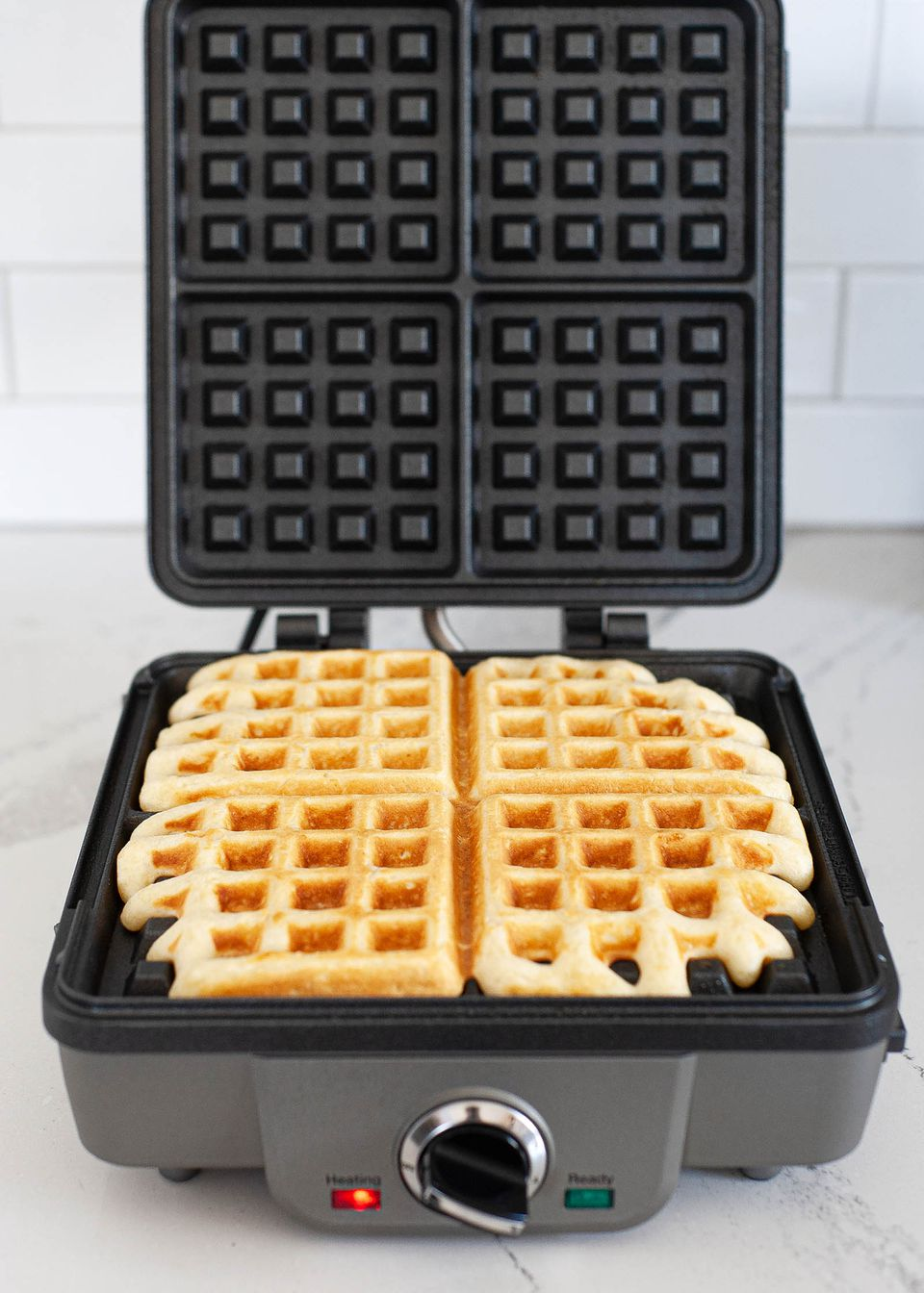 An open waffle maker with a cooked waffle inside.