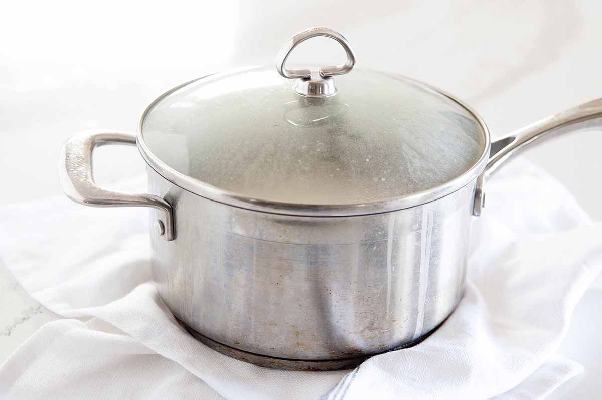 Side view of a pot of white rice steaming with the lid on. The pot is on a white linen that is on a white background.