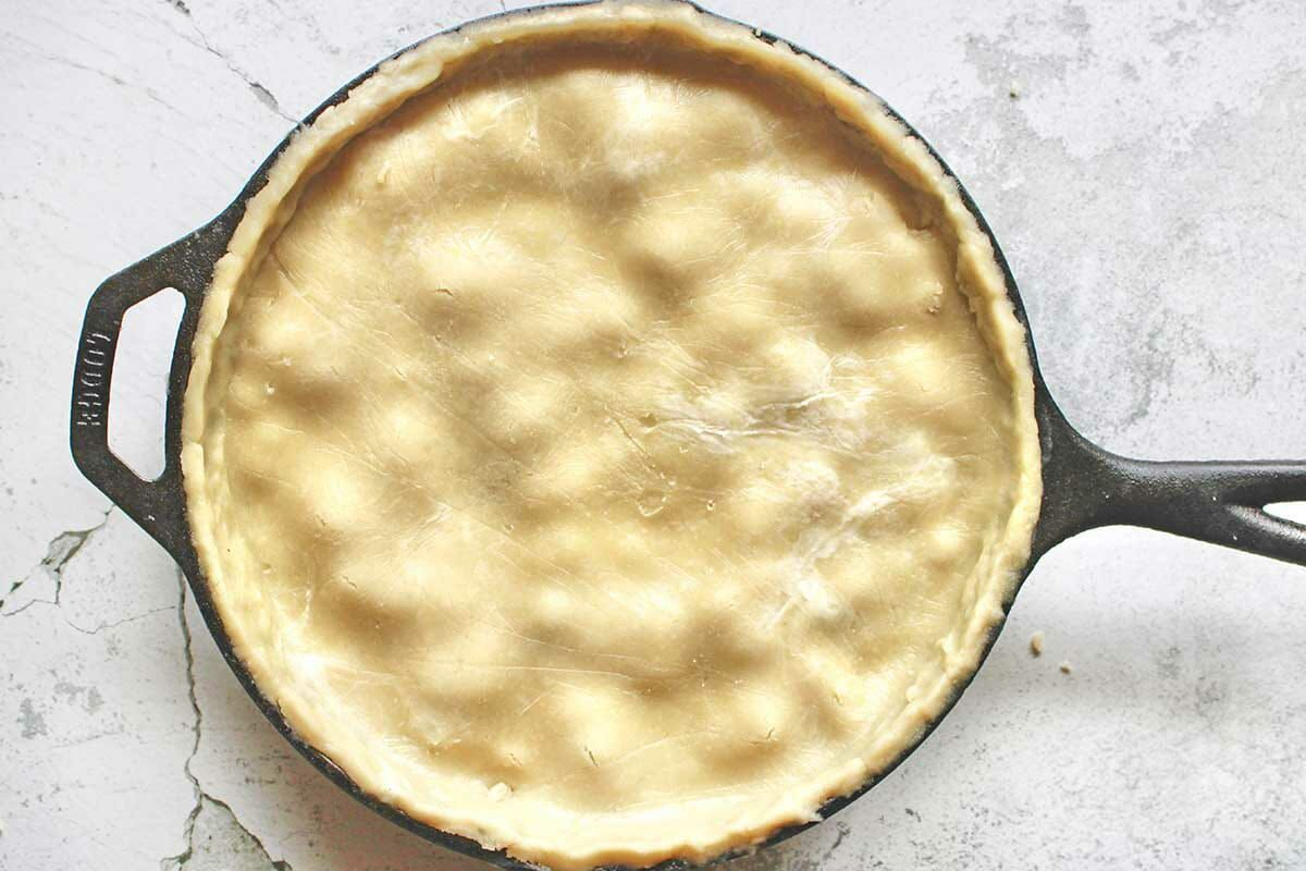 Easy Vegetarian Pot Pie in a cast iron skillet with an unbaked pie crust covering it.