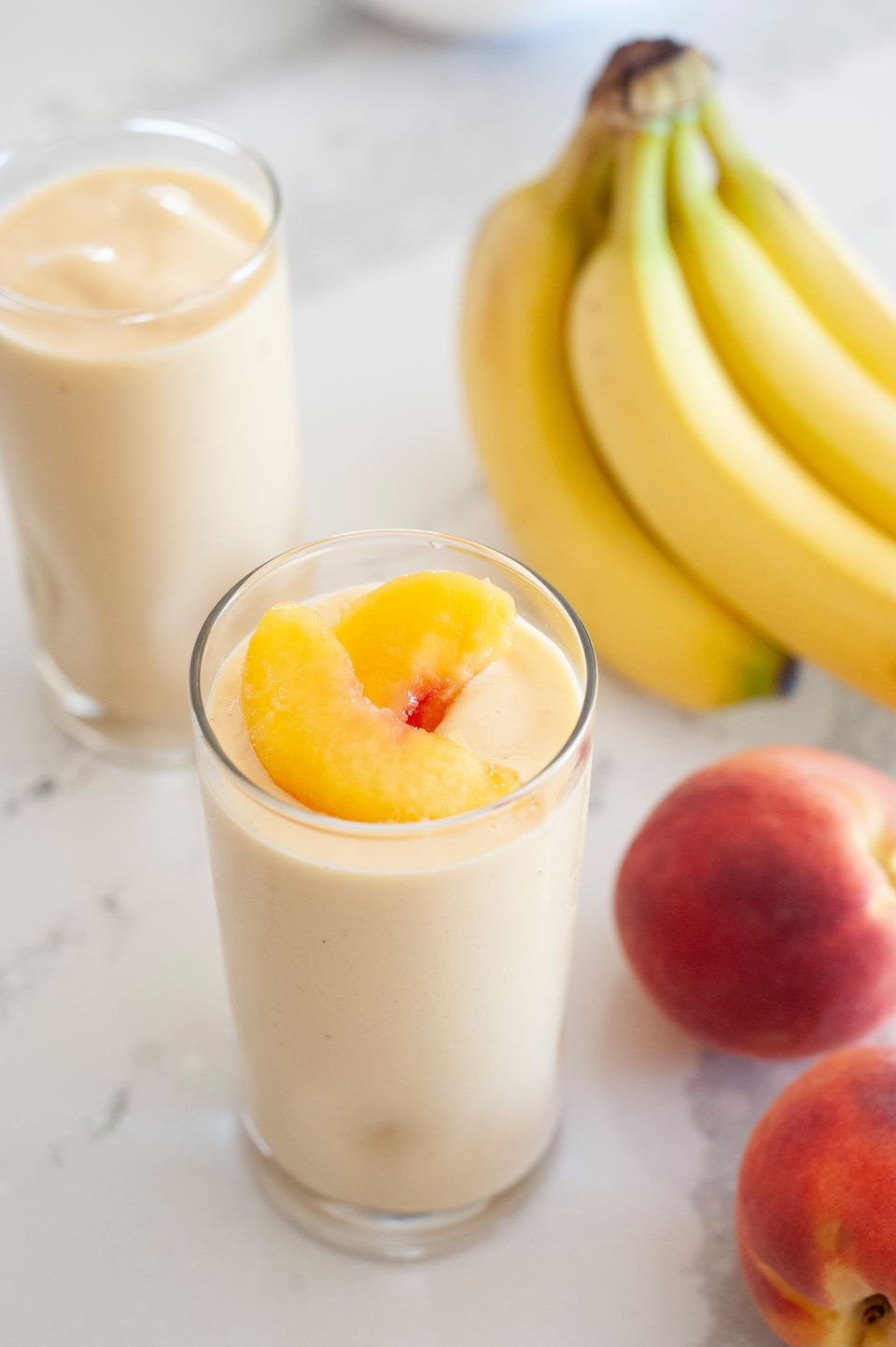 Peaches 'n' cream smoothie topped with sliced peaches and fresh fruit and a second smoothie around the glass.