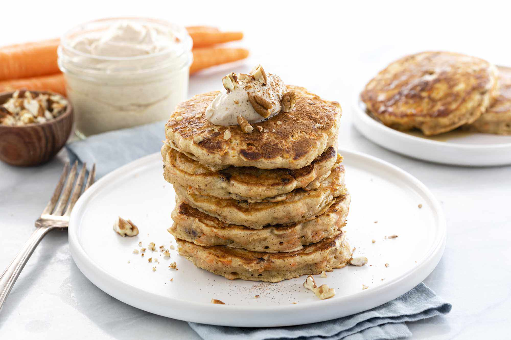 A tall stack of easy carrot cake pancakes on a white plate with chopped pecans and cream cheese topping. A linen is under the plate and a fork is to the left of the plate. Whole carrots, a container of cream cheese topping and a bowl of chopped pecans is to the upper left of the photo. A second plate of pancakes is in the upper right.