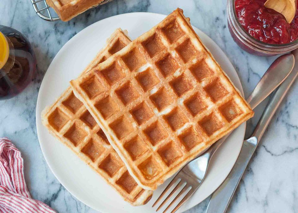 Easy waffle recipe , served on a small plate with a fork and knife nearby