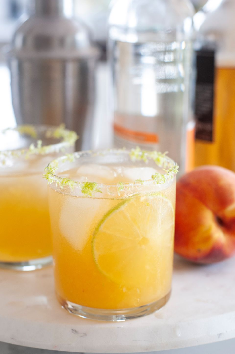 Peach margarita cocktails on a tray along with a cocktail shaker.