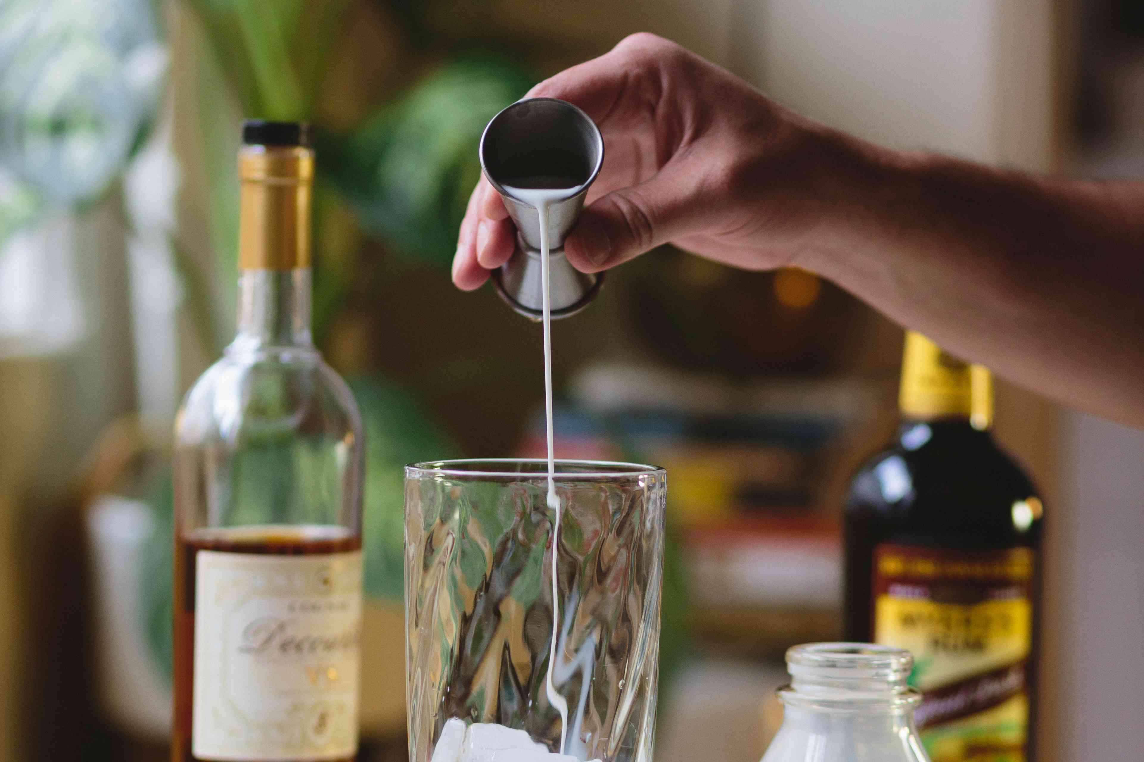 A shot is poured into a glass to make Brandy Milk Punch.