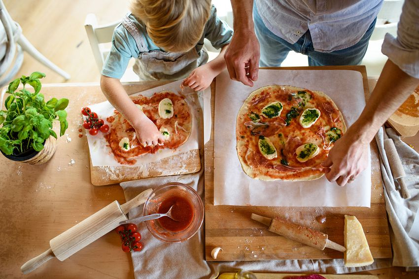 View from above of father with small son making pizza at home, cooking