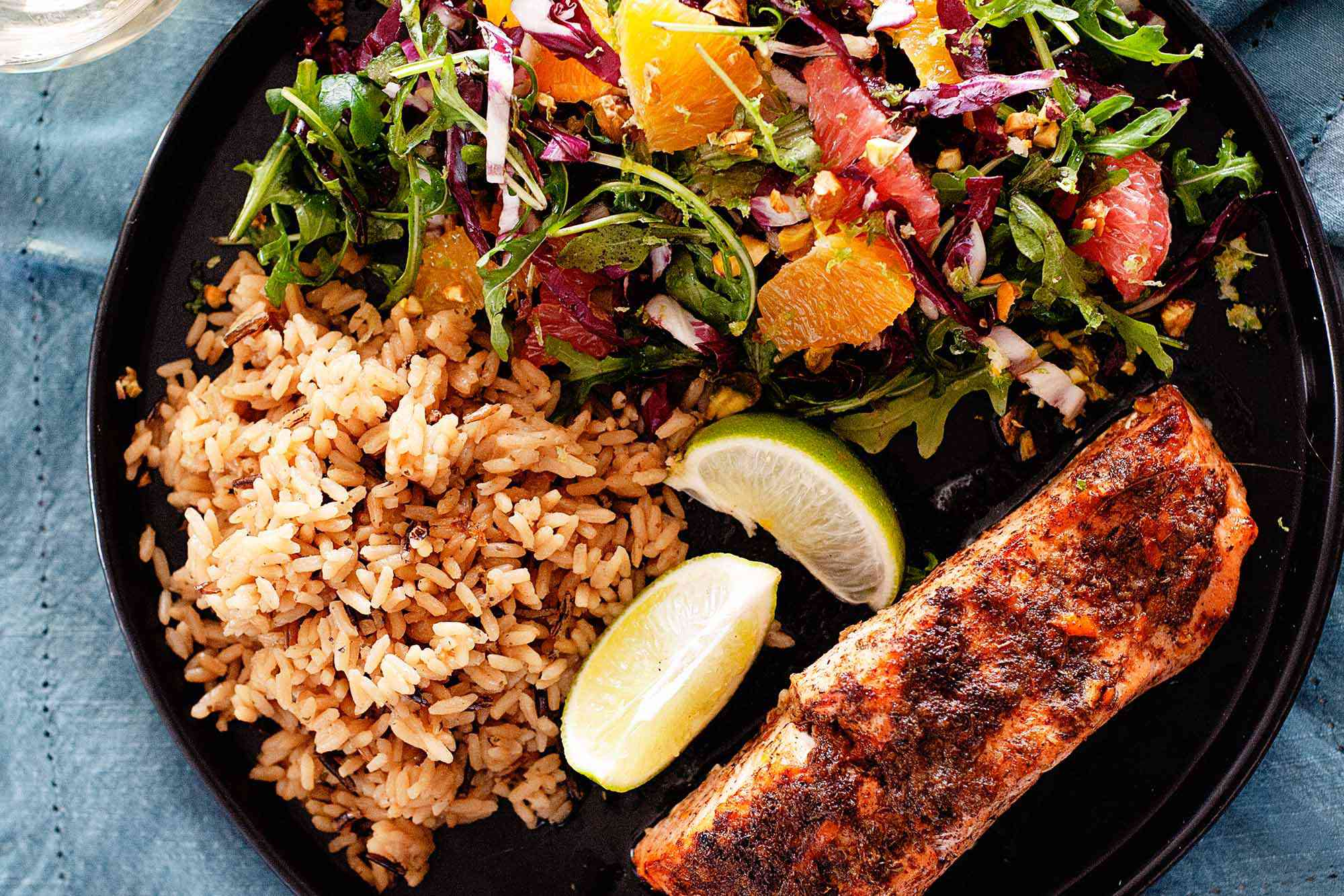 A blackened fillet of weeknight jerk salmon is on the lower right of a black plate. Lime wedges, red rice and a mixed green salad with citrus mixed in is to the left of the salmon. The plate rests on a blue linen.