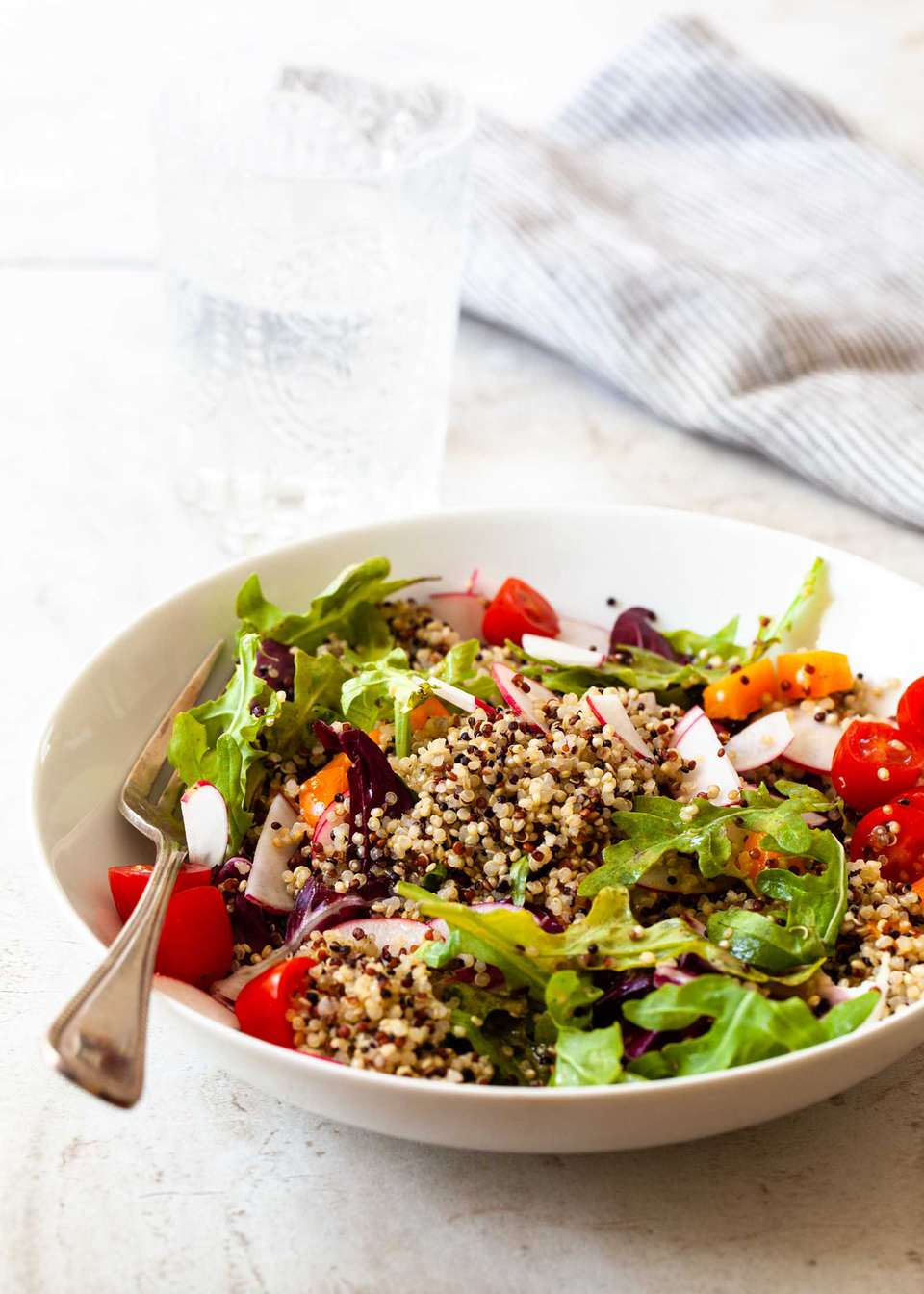 Perfect quinoa in a bowl along with lettuce, tomatoes, radish and a fork.