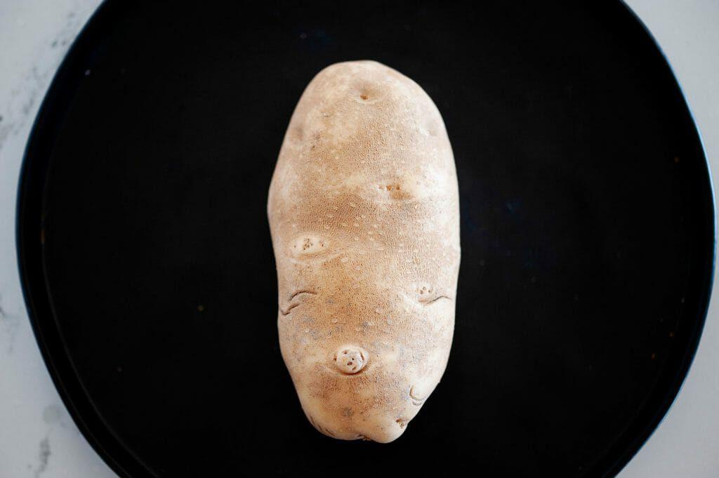 A russett potato on a black plate.